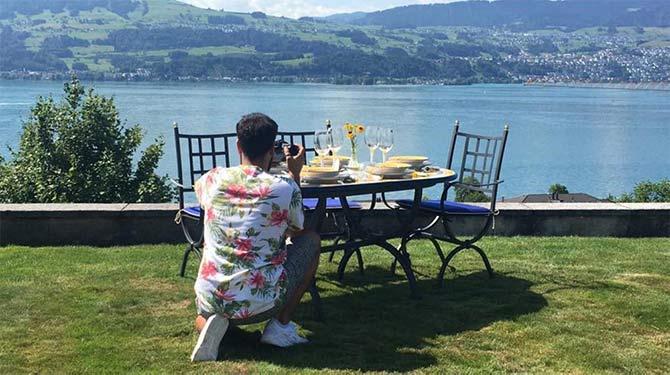Mann in Hemd fotografiert italienischen Tisch auf Terrasse