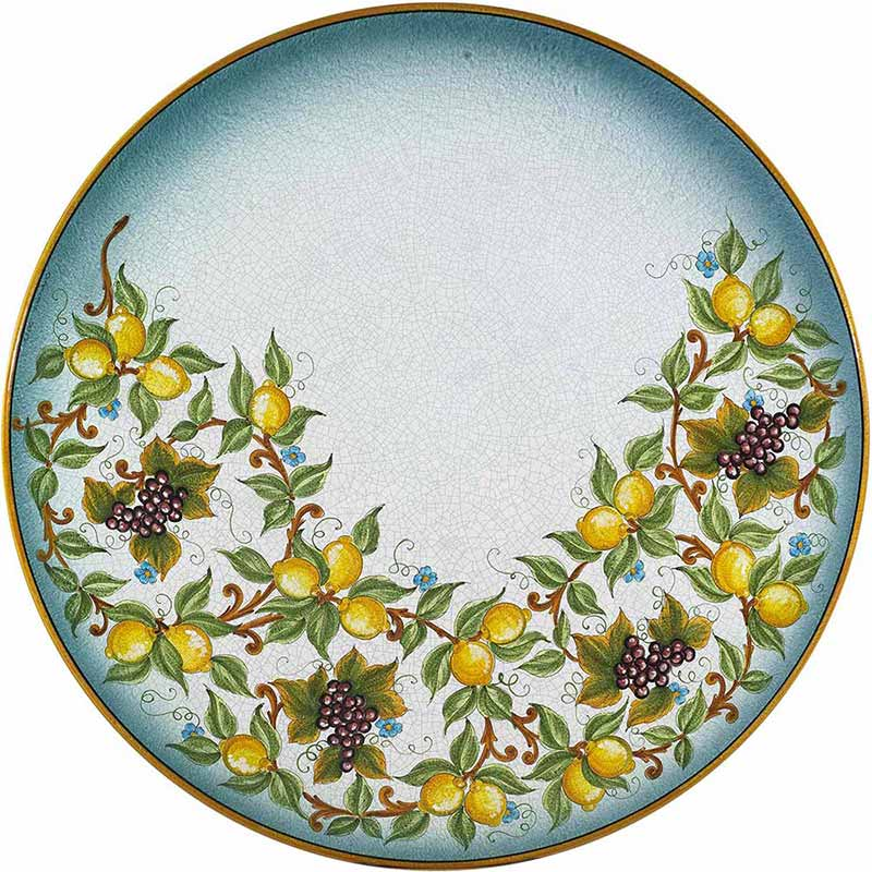 Runde Tischplatte handbemalt mit Früchten und Blättern auf blauem Grund